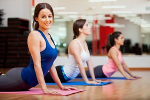 3 women doing exercise in the yoga class on yoga mats inside gym